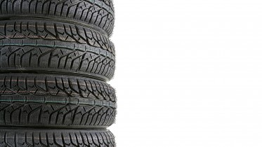 Pile of four winter car tyres with white copy space
