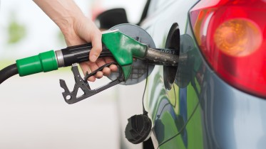 transportation and ownership concept - man pumping gasoline fuel