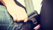transportation and vehicle concept - man fastening seat belt in